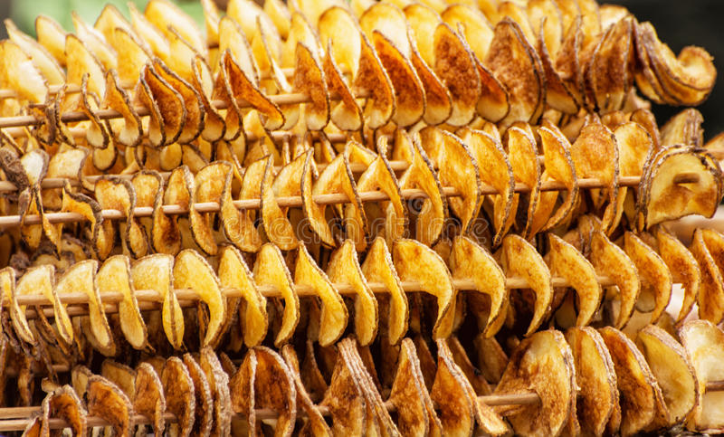 Taglio smerlato delle patate nella forma a spirale infilzata sugli stuzzicadenti immagine stock libera da diritti