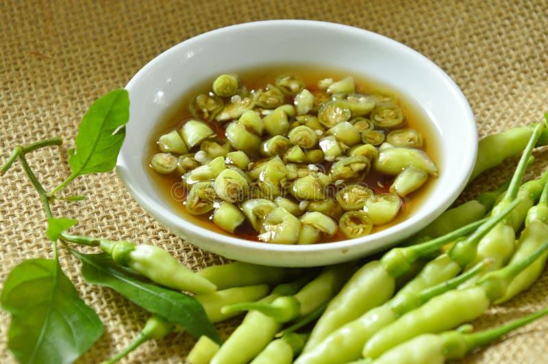 Taglio verde del peperoncino rosso e misto freschi in salsa di pesce sulla tazza fotografia stock
