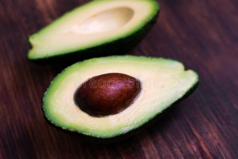 Taglio verde dell'avocado a metà sul bordo di legno fotografie stock