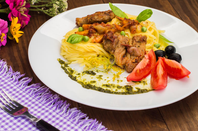 Tagliolini with meat in tomato sauce, olives and spinach. Wooden background. Close-up. Top view. Tagliolini with meat in tomato sauce, olives and sauce with royalty free stock image