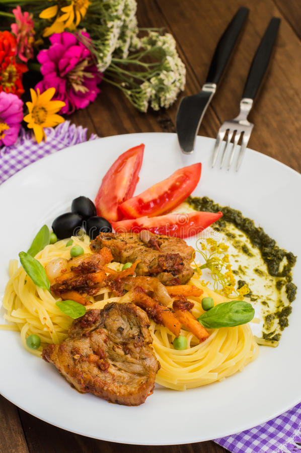 Tagliolini with meat in tomato sauce, olives and spinach. Wooden background. Close-up. Top view. Tagliolini with meat in tomato sauce, olives and sauce with stock images