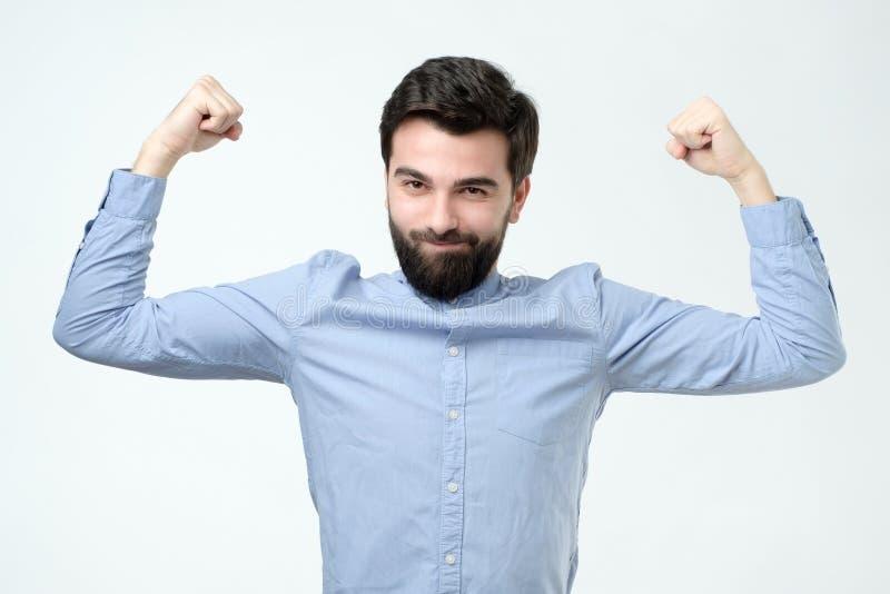 Tagnävar för den starka mannen, iklädd tillfällig blå skjorta, firar hans seger arkivfoto
