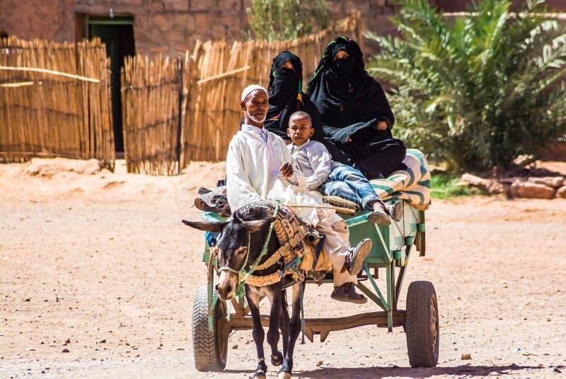 Tagounite, Maroc - 10 octobre 2013 La vie sur la rue - équitation de famille sur l'âne avec le chariot photos stock