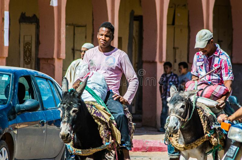 Tagounite, Maroc - 10 octobre 2013 La vie sur la rue - hommes montant sur les ânes photo stock
