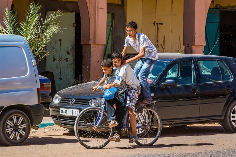Tagounite, Maroc - 10 octobre 2013 La vie sur la rue - trois enfants montant sur un vélo images stock