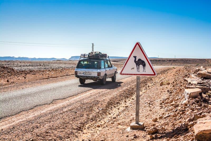 Tagounite, Maroc - 10 octobre 2013 Panneau routier avec le chameau dans le désert avec le cru outre de la voiture de route photos libres de droits