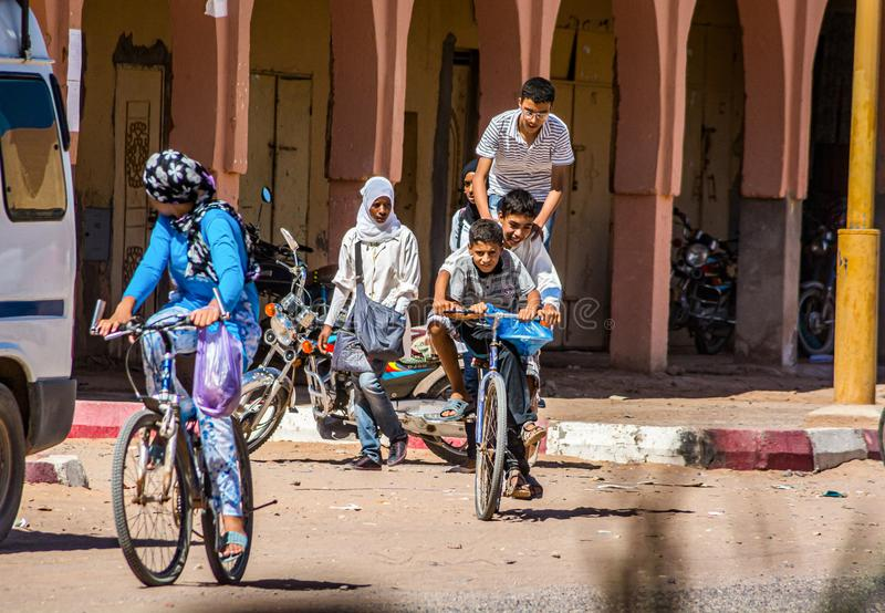Tagounite, Marocco - 10 ottobre 2013 Vita sulla via - tre bambini che guidano su una bici immagine stock
