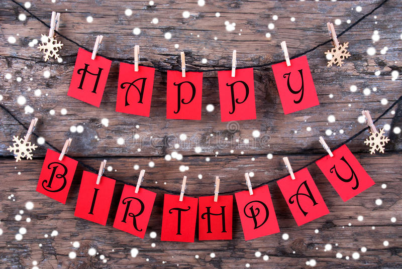 Tags With Happy Birthday Wishes in the Snow. Many Red Tags with Happy Birthday Wishes on a Line Hanging in the Snow in front of a Rustic Wooden Panel royalty free stock photo
