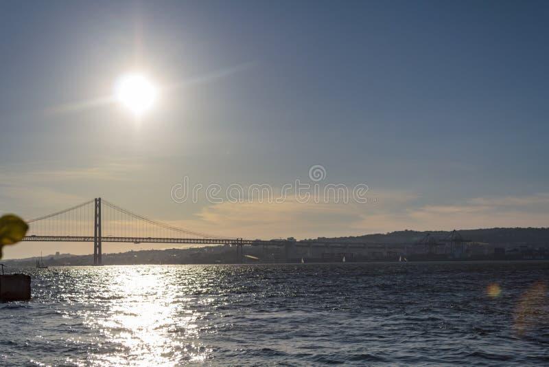 Tagus River och Lissabon 25 av den April bron på solnedgången arkivbild