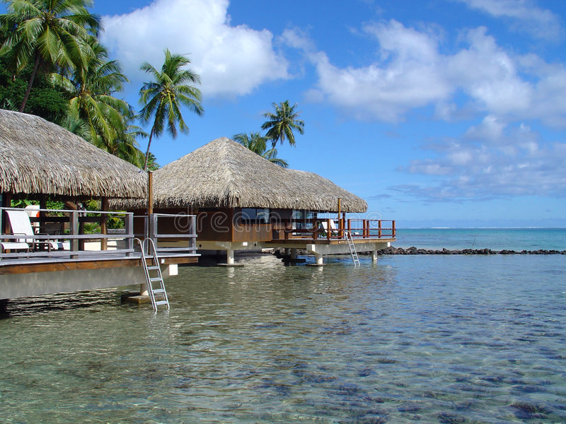 Tahiti Resort. Bungalows on stilts over the tropical water of the South Pacific stock images