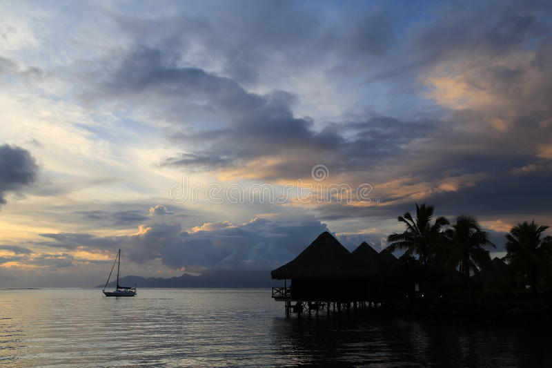 Tahiti sunset. With boat and over water bungalows royalty free stock photo