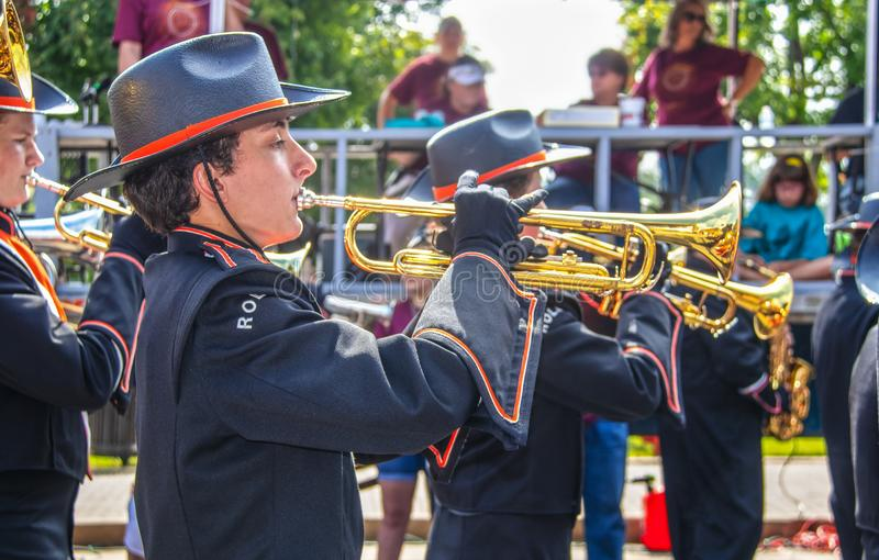 Tahlequah USA High school band members in cowboy hats and black uniforms and gloves play trumpets in front of reviewing stock photo