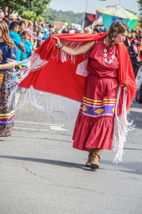 Tahlequah USA - Native American woman in traditional dress and cowboy boots swirls her red fringed cape as she walks in. 8-31-2019 Tahlequah USA - Native stock photos