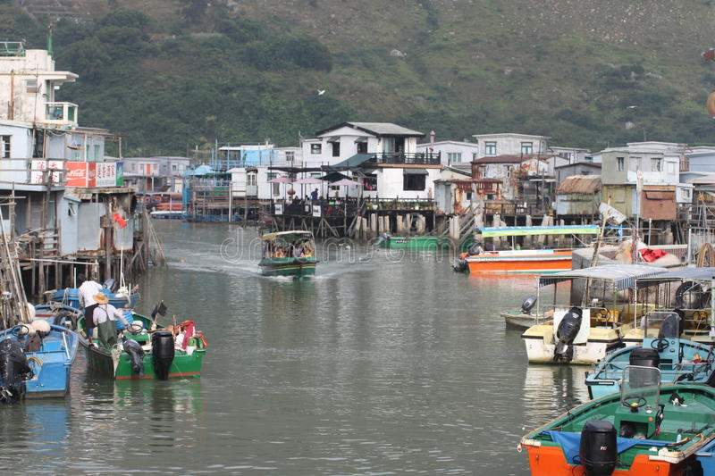 Tai O village on stilts, on Lantau Island, Hong Kong. Tourist boat and local fishing boats with houses on the water in the background royalty free stock photo