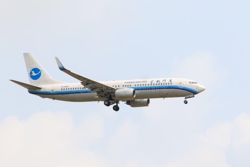 TAILÂNDIA, BANGUECOQUE 3 DE MARÇO: Voo do plano da linha aérea de Xiamen acima do suvarn fotografia de stock