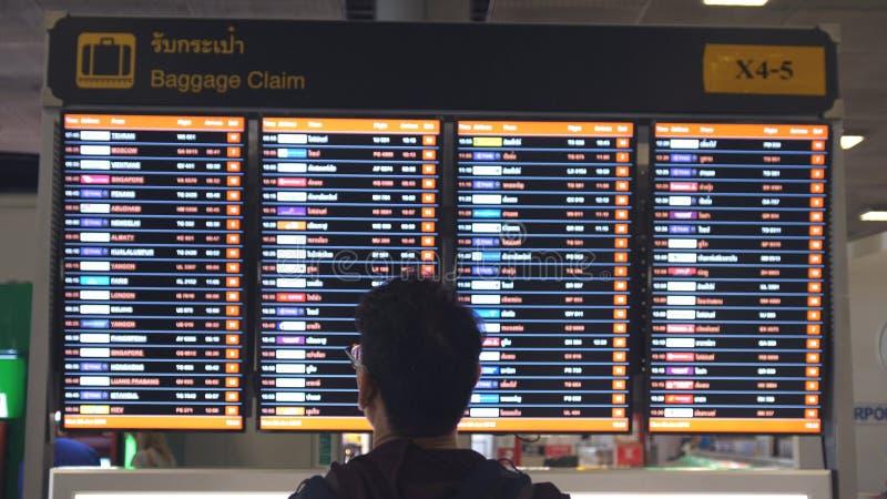 Tailândia, Banguecoque, o 29 de janeiro de 2018 Equipe o passageiro que chega e que olha o calendário da reivindicação de bagagem foto de stock royalty free