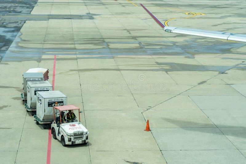 Tailândia, Don Muang International Airport, Banguecoque, - 23 de julho de 2018: Transporte troles com bagagem carregada na pista  fotografia de stock