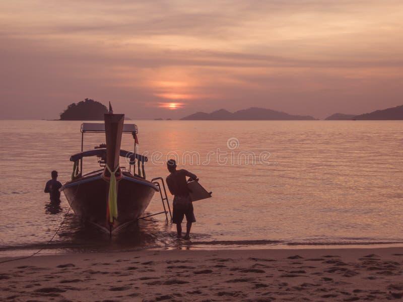 Tailândia - homem dois que trabalha com o barco estacionado na costa pelo por do sol fotografia de stock royalty free
