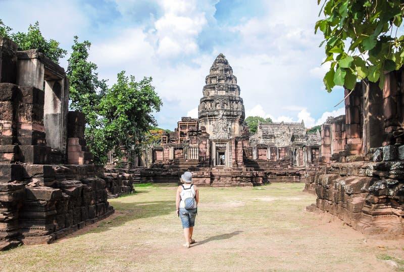 Tailândia, o 1º de junho de 2011 Turista da jovem mulher que aprecia uma vista do templo velho Prasat Hin Phimai, no parque histó imagens de stock