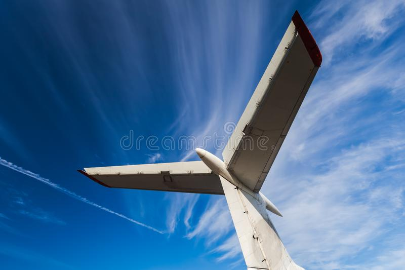 Tail of aircraft. White tail of aircraft on blue sky background. Passenger airplane, view with behind. Tail of an aircraft stock images