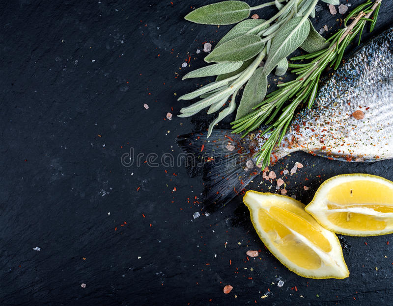 Tail of fresh raw Dorado or sea bream fish on black slate stone board with spices, herbs, lemon and salt royalty free stock image