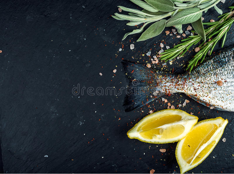 Tail of fresh raw Dorado or sea bream fish on black slate stone board with spices, herbs, lemon and salt. Top view, copy space royalty free stock image