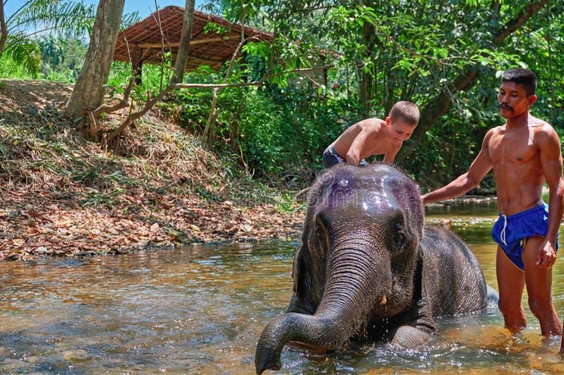 TAILÂNDIA, PHUKET, o 23 de março de 2018 - o menino 10 anos velho está nadando no rio com o elefante para o projeto do estilo de  fotografia de stock