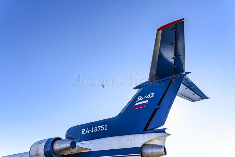 Tail of a short-range three-engine passenger aircraft Yak-42 NATO codification: Clobber and a bird in the sky. royalty free stock photo