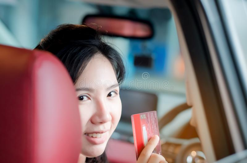Tailandés feliz de la mujer que se sienta dentro de su nuevo coche que muestra la tarjeta de crédito, mujeres Asia fotos de archivo libres de regalías