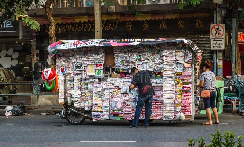 TAILAND, BANGKOK – MARCH 3, 2015: Asia street life, man buys a newspaper at the newsstand royalty free stock photo