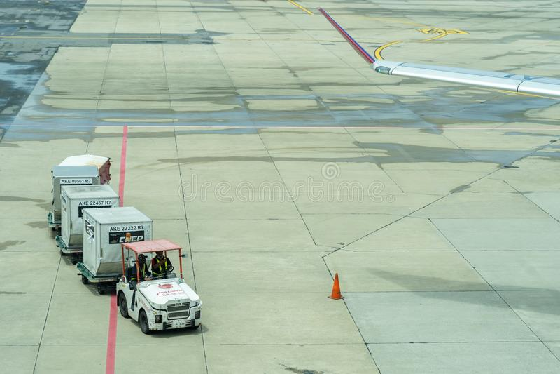 Tailandia, Don Muang International Airport, Bangkok, - 23 de julio de 2018: Flete las carretillas con equipaje cargado en la pist fotografía de archivo