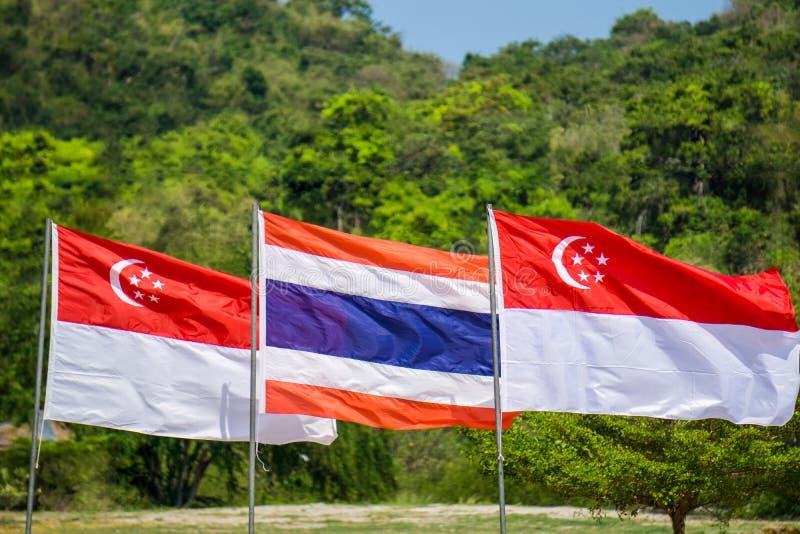 Tailandia y Singapur señala soplado por medio de una bandera en la asta de bandera con la más forrest foto de archivo