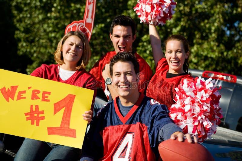 Tailgating: Aufgeregte Fans, die für Team And Holding Sign zujubeln stockfotografie