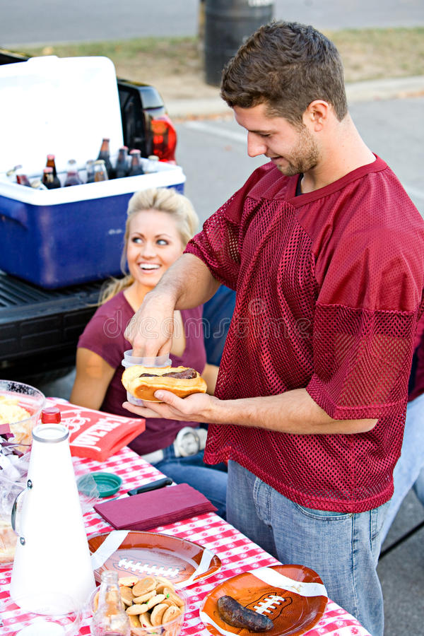 Tailgating: Guy Getting Food At Tailgate-Partei lizenzfreies stockbild