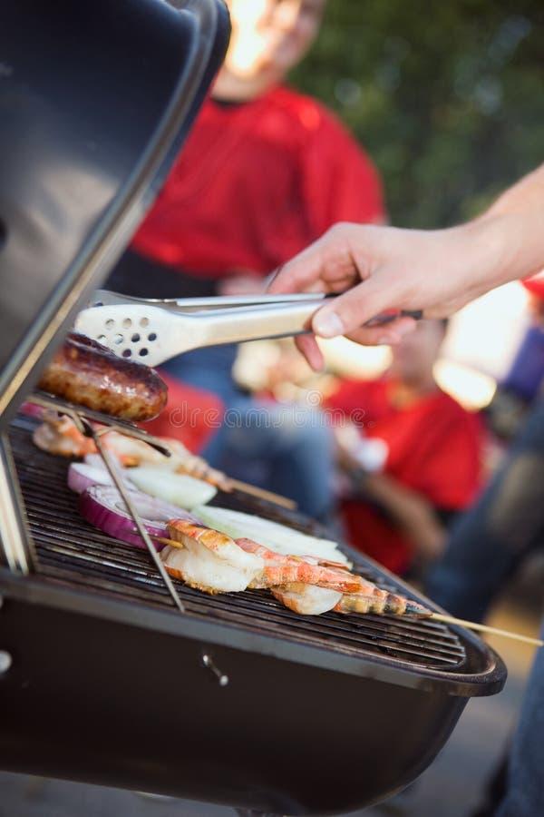 Tailgating: Mann, der Würste und anderes Lebensmittel für Heckklappen-PA grillt stockbilder