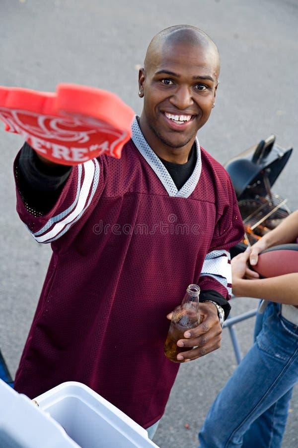 Tailgating: Team Football Fan Points To-Kamera während der Partei stockbild
