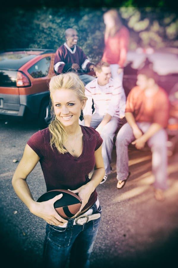 Tailgating: Vrouwelijke Voetbalventilator met Vrienden op Achtergrond stock foto
