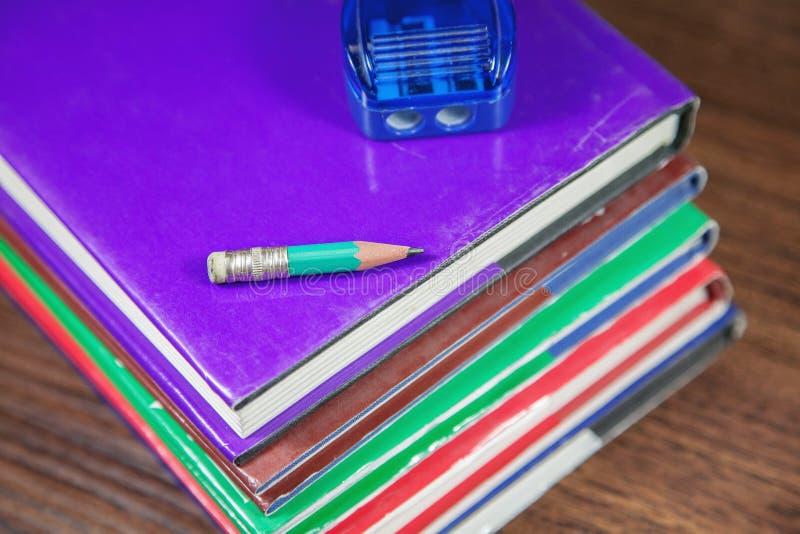 Taille-crayons avec le petit crayon sur la pile de livres image stock