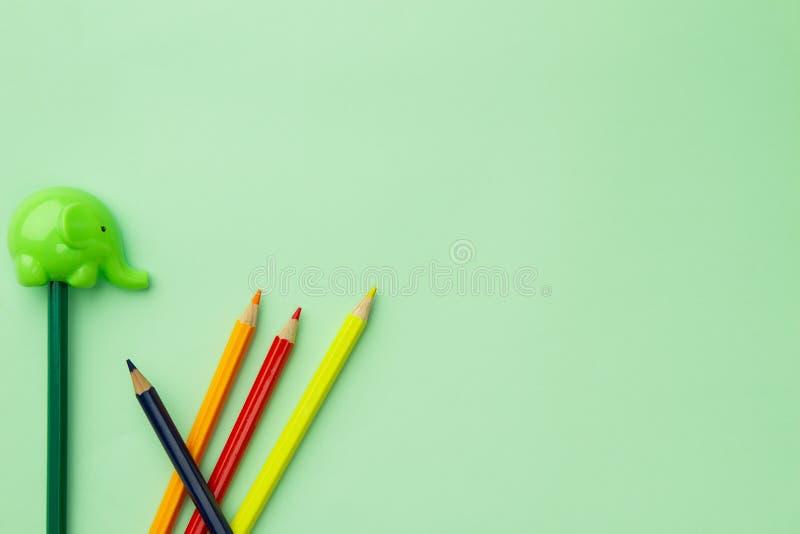 Taille-crayons sous forme d'éléphant et cinq crayons chaotiques sur un fond vert pâle photos libres de droits