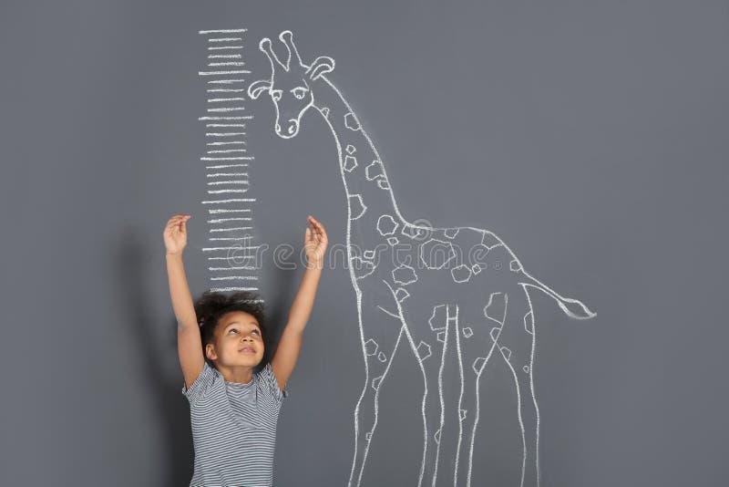 Taille de mesure d'enfant afro-américain près du dessin de girafe de craie sur le gris image stock