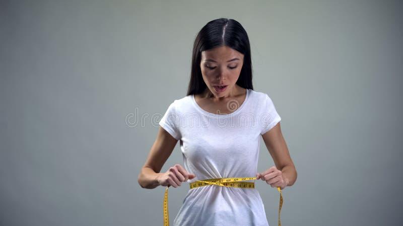 Taille de mesure de femme asiatique avec la bande, désir de perdre le poids, risque d'anorexie photos stock