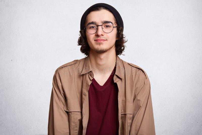Taille herauf Atelieraufnahme des begeisterten ruhigen Kerls, der, betrachtend direkt Kamera, tragende beige Jacke, rotes Sweatsh stockfotografie
