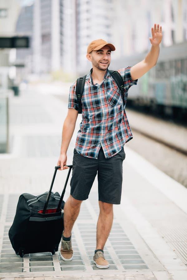 Taille herauf das Porträt des gut aussehenden Mannes die Hand anhebend, die weg schaut und am Bahnhof lächelt lizenzfreie stockfotografie