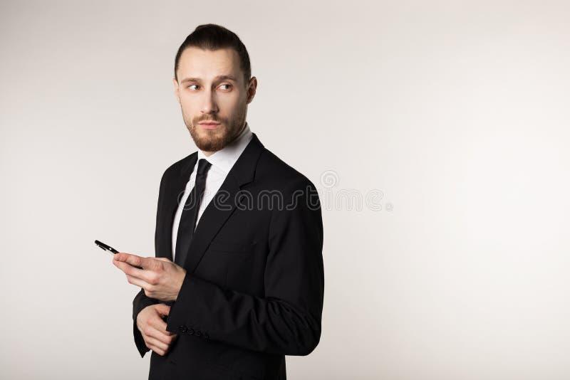 Taille herauf das Porträt des jungen bärtigen Mannes in der schwarzen Anzugsstellung mit Stift in der Hand, weg schauend stockfotos
