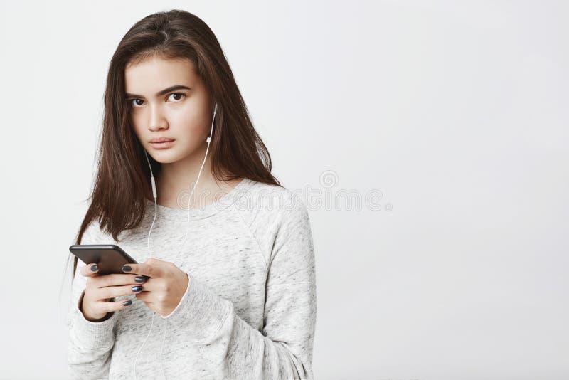 Taille herauf den Schuss des schönen netten europäischen Mädchens mit dem langen braunen Haar, Smartphone beim Musik herein hören stockfotografie