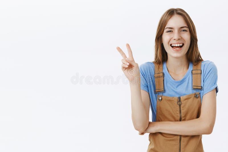 Taille-oben geschossen von der netten freundlichen europäischen netten Frau in den braunen Jeansstoffen, die Friedenszeichen oder lizenzfreie stockfotografie