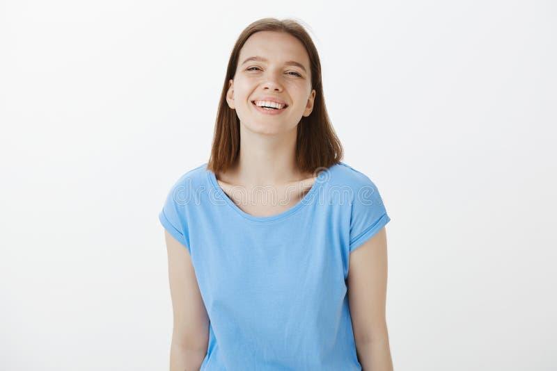 Taille-oben schoss vom positiven glücklichen jungen weiblichen Mitarbeiter in der zufälligen Ausstattung, breit lächelte und star stockbild
