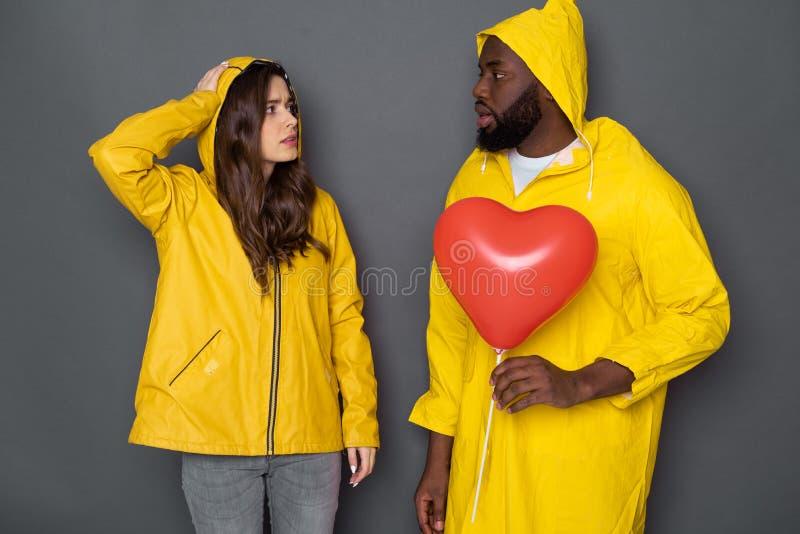 Taille oben von den betonten jungen Paaren, die gelbe Regenmäntel gegen grauen Hintergrund tragen stockbilder