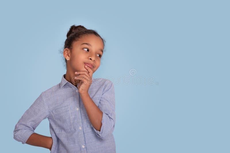 Taille omhoog emotioneel portret van mulattameisje op blauwe achtergrond in studio Zij raakt haar kin en denkt over iets stock fotografie