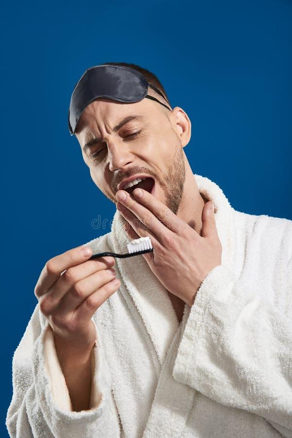 Taille omhoog van de jonge slaperige mens die tandenborstel in wapen houden royalty-vrije stock afbeelding